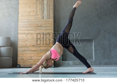 Young slim blond woman in yoga class making exercises. Girl do One-Legged Downward-Facing Dog Pose. Healthy lifestyle in fitness club. Stretching