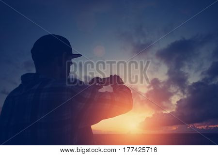 Silhouette of a young man taking photo of sunset with mobile phone