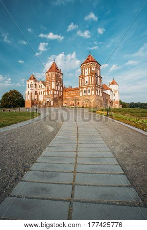 Mir, Belarus. Pathway To Mir Castle Complex On Blue Sunny Sunset Sky Background. Architectural Ensemble Of Feudalism, Cultural Monument, UNESCO Heritage. Famous Landmark In Summer