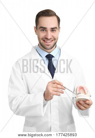 Handsome young dentist with jaw model and mirror on white background