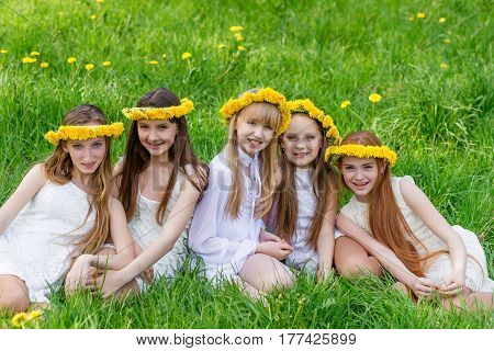 Girlfriends Are Sitting In The Grass With Wreaths Of Dandelions On Their Heads In The Open Air