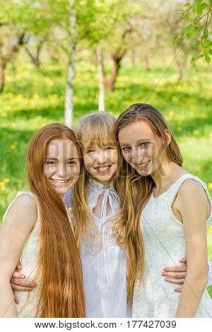 Three beautiful young girls in white dresses in summer park