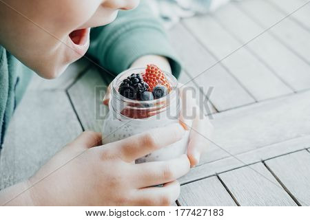 Boy Eating Pudding With Chia Seeds, Yogurt And Fresh Fruits: Strawberries, Blueberries And Blackberr