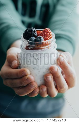 Vertical Photo Boy Hands With Pudding With Chia Seeds, Yogurt And Fresh Fruits: Strawberries, Bluebe