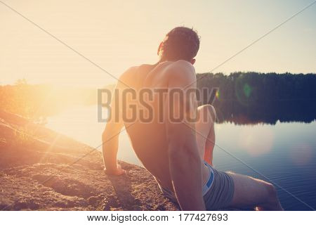 Muscle young man sitting on the cliff near lake and looking far away at sunset