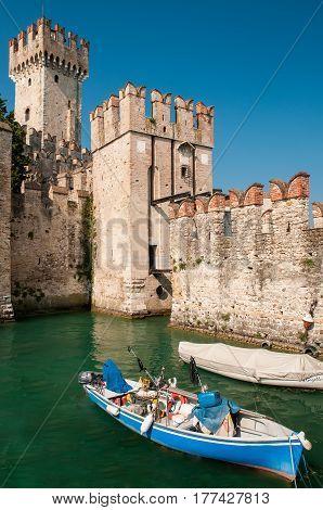 Fisher boat near Scaliger Castle on lake Garda Sirmione Italy