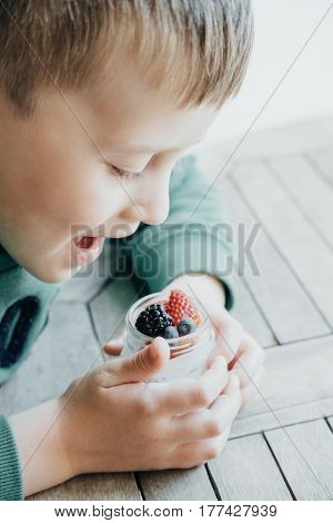 Cute Boy Eating Pudding With Chia Seeds, Yogurt And Fresh Fruits: Strawberries, Blueberries And Blac