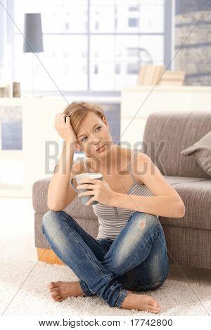 Junge Frau sitzen auf Boden zu Hause denken mit Tee in der hand.?