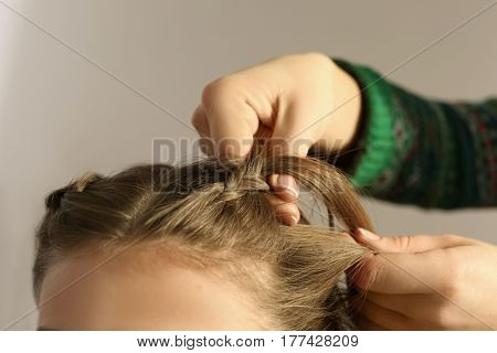 Hairdresser doing hairstyle to young woman