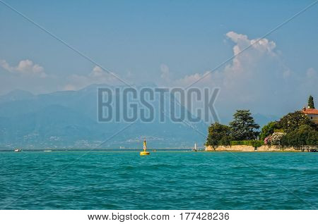 Scenic view of lago di Garda - Garda Lake - with azure water yellow buoy blooming plants on the coast and alp mountains on background Italy
