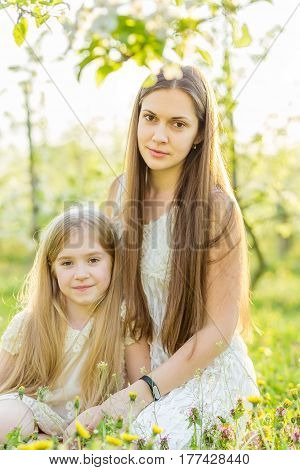 Beautiful Mother And Daughter In A Blooming Garden In The Spring