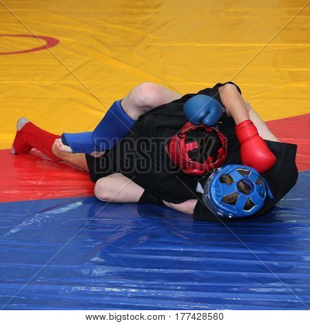 Two young fighters in sports protection on the wrestling mat cover
