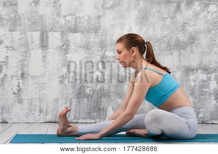 Fit sporty woman exercising on blue mat indoors. Young attractive woman wearing sportswear practicing yoga.