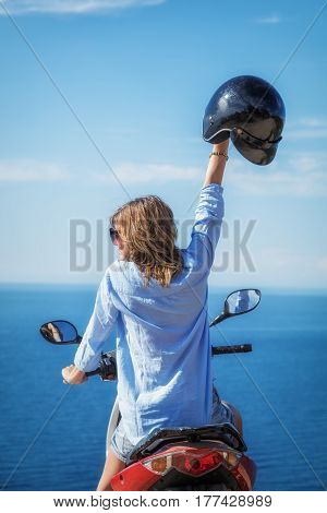 Girl enjoying the ocean / sea view with her scooter.