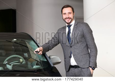 Handsome single man chooses a car in the showroom