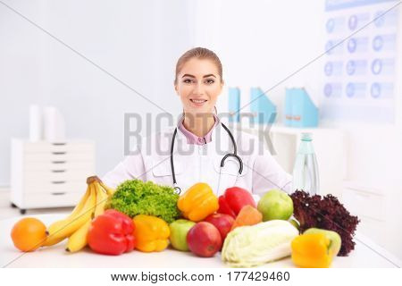 Young female nutritionist with vegetables and fruits in her office