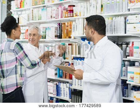 Chemist Holding Clipboard While Looking At Colleague And Custome