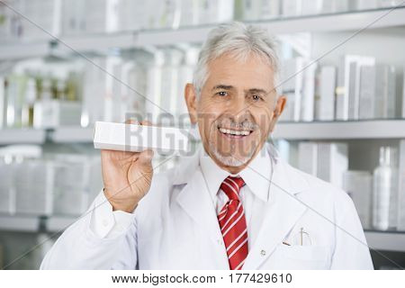 Smiling Pharmacist Holding Medicine Box Against Shelves