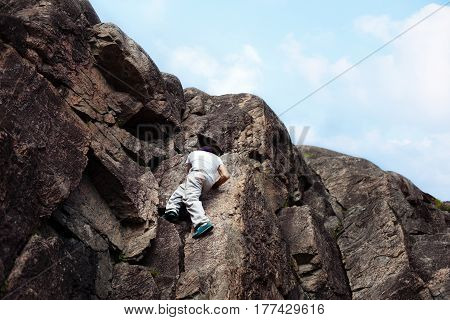Young risky man passing over danger mountain without safety rope