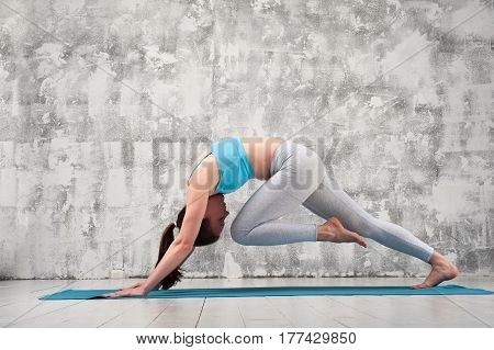 Young sporty woman wearing sportswear practicing yoga indoors. Fit flexible girl exercising on blue mat against grey wall.