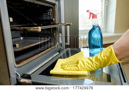 Man With Bottle Of Spray And Rag Cleaning Oven