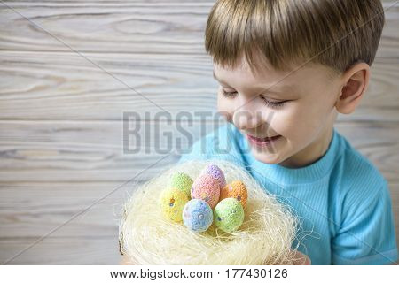 Cute Little Boy Holding A Nest With Colored Easter Eggs At Home