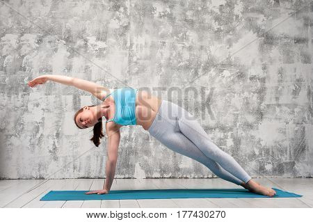 Fit attractive woman staying in side plank yoga position indoors. Sporty girl exercising on blue mat against grey wall.