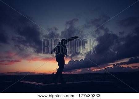 Silhouette of a young casual man walking balance on top of the roof in the city at sunset