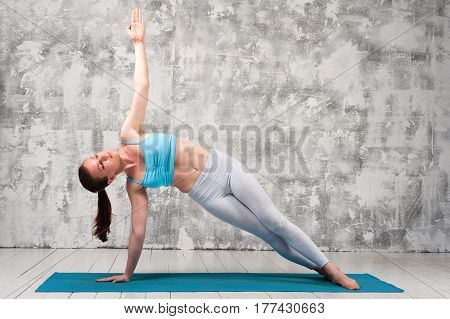 Side view of young woman practicing yoga indoors. Fit girl wearing sportswear doing plank exercise on blue mat