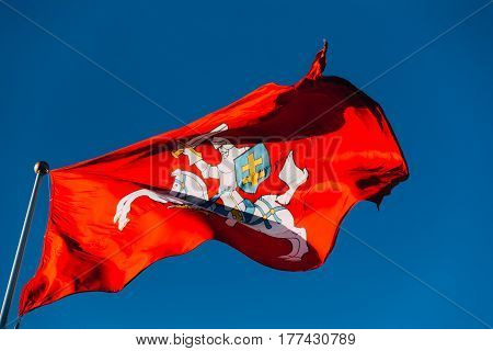 Coat Of Arms Of Lithuania On The State, Historical, Flag Of Lithuania, Waving On Flagpole At Blue Sunny Sky Background.