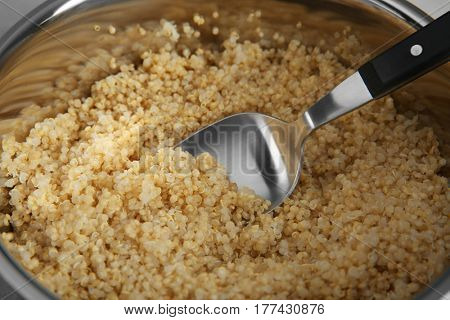 Boiled sprouted organic white quinoa grains in saucepan, closeup
