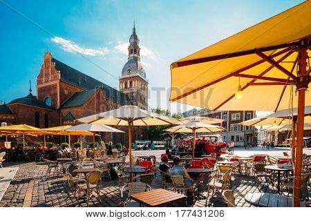Riga, Latvia - July 1, 2016: People Resting On Dome Square In Sunny Summer Day. Dome Cathedral On Background Under Blue Sky.