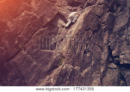 Young risky man climbing over danger mountain without safety harness