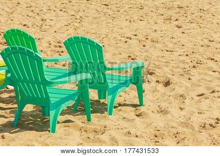 Rest and relax in summer. Three green plastic chairs on sand. Relaxation place on sunny beach.