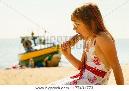 Summertime joy summer recreation outside concept. Toddler girl in eyeglasses eating ice cream on beach
