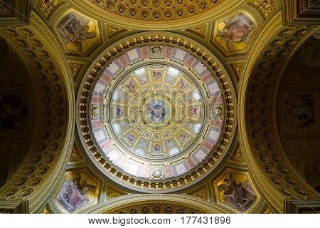 BUDAPEST, HUNGARY - FEBRUARY 22, 2016: Interior of the cupola. Roman catholic church St. Stephen's Basilica. Richly decorated ceiling with mural and gold details. Painted scenes from the Bible.