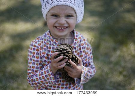 little girl in knitted white cap is collecting cones in the forest and laughing