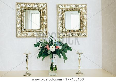 Beautiful bouquet in glass vase between candlesticks and luxury mirrors hanging on wall