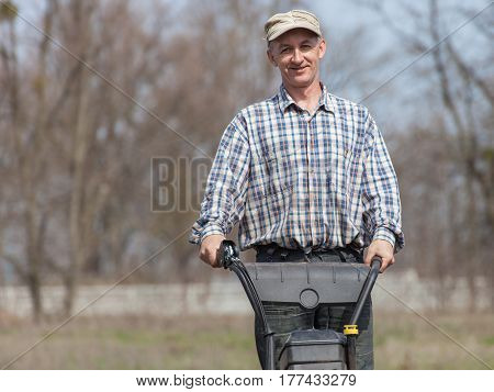 Portrait of smiling farmer. Man working in the garden with garden tiller. Man with tractor cultivating field at spring. Farmer loosens soil by petrol cultivator