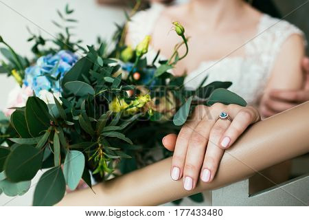Beautifully decorated bouquet of pink roses, white and blue flowers and different green petals and bride's hand with ring