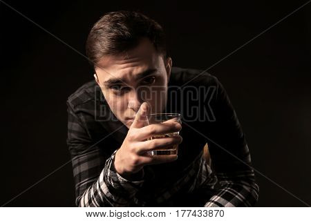 Handsome depressed man with glass of alcohol on black background