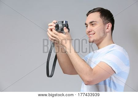 Handsome young tourist taking photo on grey background