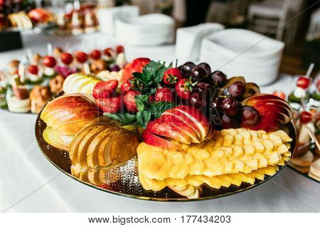 Beautifully decorated catering banquet table with different food snacks and appetizers with sandwich, canape and fresh fruits