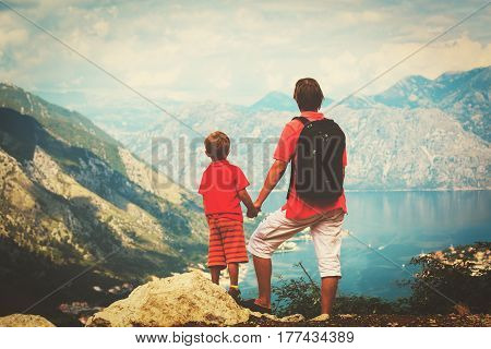 family travel - father and little son hiking in mountains at sea