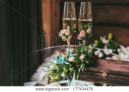Two newlyweds glasses with champagne decorated with small boutonniere