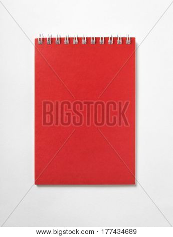 Red open Notepad with spiral binding, top view, white background