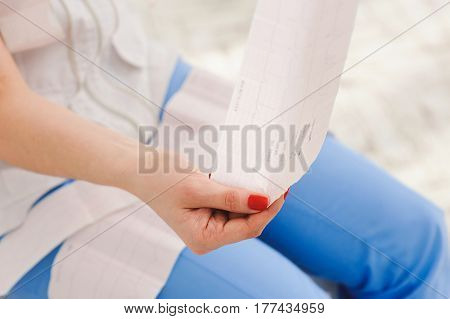 Electrocardiogram, ecg in hand, palm of doctor. Medical health care. Clinic cardiology heart rhythm and pulse test closeup. Cardiogram printout