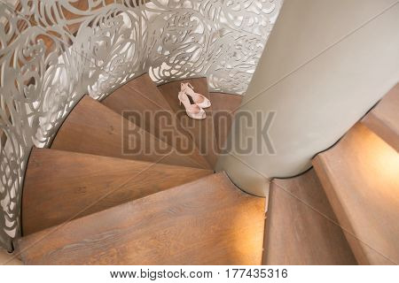 Pair of elegant brides biege shoes on wooden spiral stairs, top view