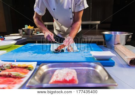 Sushi chef cuts the eel on blue cutting board in the kitchen