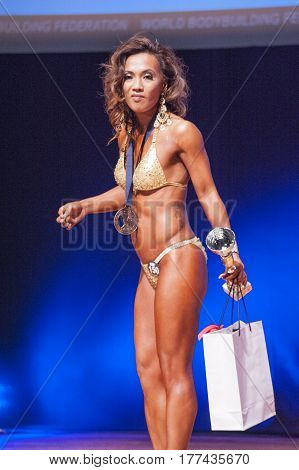 MAASTRICHT THE NETHERLANDS - OCTOBER 25 2015: Female physique and bikini model Esther Blom celebrates her victory on stage at the World Grandprix Bodybuilding and Fitness of the WBBF-WFF